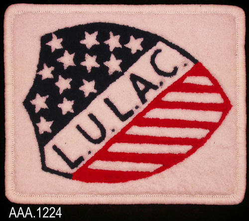 "This artifact is a small, white rug.  In the center of the rug is a shield of red and dark blue fibers.  Initials in the shield read:  ""L.U.L.A.C."""