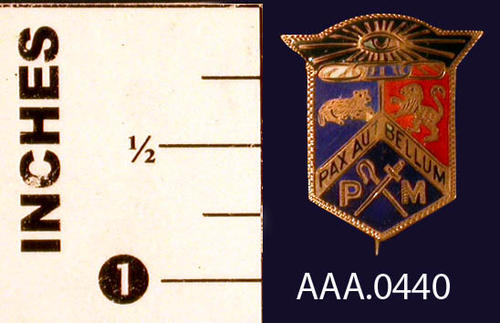 "This artifact is a pin  It is from the Odd Fellows Lodge and Rebekah Assembly. It has a coat of arms shaped (shield with the latin words, ""Pax Aut Bellum"" (Peace or War) over crossed swords and the letters, ""PM."" Donor's Remarks:  This pin belonged to Alys W. Tuthill and depicted an office she held in the Rebekah Lodge."