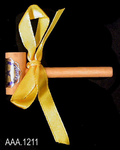 "This artifact is a small wooden gavel made from a 1/2"" piece of dowel used for the head of the gavel, and a 1/4"" piece of dowl used for the handle.  A small, yellow, cloth bow is on the handle with a blue and gold American Legion sticker on the head of the gavel.  The gavel measures 2 1/2"" in length."