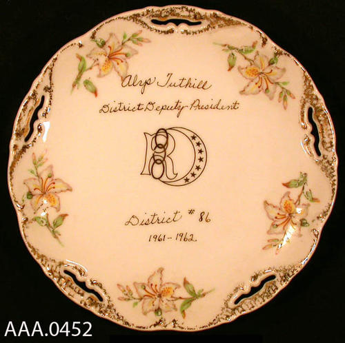 "This artifact is a plate.  It is from the Odd Fellows Lodge and Rebekah Assembly.  This china plate has the following text printed on the fact of the plate:  "" Honoring Alys Tuthill, with District Deputy President, District #86, 1961-1962.""  The Rebekah logo is also printed on the fact of the plate. Donor's Remarks:  This plate was given to Alys Tuthill by Roxie Jerman and Bertha Baer in recognition as being President of the Rebekah District."