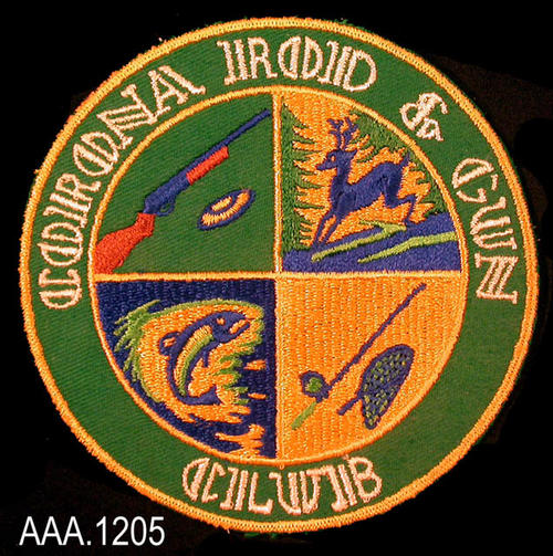 This artifact is a patch from the Corona Rod and Gun Club.  The patch is divided in the center in to four sections.  Embroidered in the four sections is a depiction of a gun, deer, fish, and a rod with a net.  The background of the patch is darkgreen with yellow, blue, and brown used to embroidery the designs.