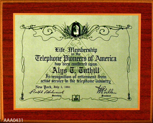 "This artifact is a wooden placque from the Telephone Co. Donor's Remarks:  This placque identifies Alys Tuthill as having been elected  a life member of the ""Telephone Pioneers of America.""  This recognition is based on length of service."
