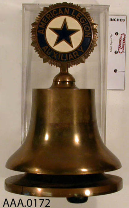 This artifact is a bronze bell with the American Legion symbol on the top end of the bell.  The bell is attached to a base of the same material.  CONDITION:  Good.