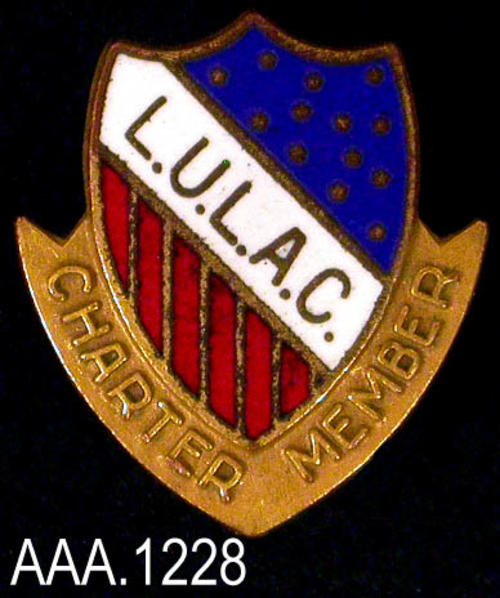 "This artifact is a Charter Member Pin of the L.U.L.A.C.  The word ""Charter"" is written on one side of the pin and ""Member"" on the other side. Both words are in raised, gold text. This shield, shaped pin has the initials, ""L.U.L.A.C."" going diagonally across the front.  Gold stars on a blue field make up the upper right portion of the shield while red and white stripes the lower left side of the shield. This pin measures 5/8"" x 5/8""."