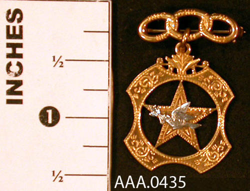 This artifact is a gold medal from the Odd Fellows Lodge and Rebekah Assembly with three chain links on top.  Hanging from the links is a  four cornered gold medal with a star in the center and a silver dove with an olive branch in its beak. Donor's Remakrs:  This was a medal given to Alys Tuthill for an office held in the Rebakah Lodge.