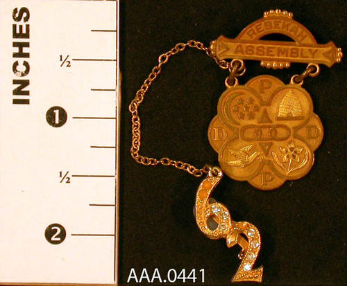 "This artifact is a gold pin.  It has an arc over a bar on top of the words ""Rebekah Assembly""  and is held by chains on an eight circle pendant with the Rebekah assemblies and letters ""PDDP.  Hanging from the pin, on a small gold chain, is the number ""62"" with small diamonds in the 6 and 2. Donor's Remarks:  This pin was given to Alys W. Tuthill when she completed a term as president of the district within the Rebekah Lodge."