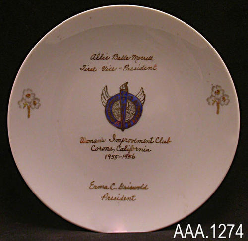 "This artifact is a white, ceramic plate measuring 6 1/2"" in diameter.  At the top of the plate in gold, cursive writing is the following text:  ""Allie Belle Morrell - First Vie-President.""  Next on each side of the plate is a flower in gold and gray.  A graphic design appears in the center of the plate between the flowers that are on the edge.  This graphic design is done in dark blue and gold.  There is a winged circle with a torch in the center.  Text on the circle reads:  ""Strength United is Stronger.""  The initials ""CFWC"" appear on the torch.  Below the graphic design is the following gold, cursive writing:  ""Woman's Improvement Club - Corona, California - 1955-1956 - Erma C. Griswold - President."""